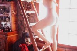 woman nude on ladder in cozy cabin