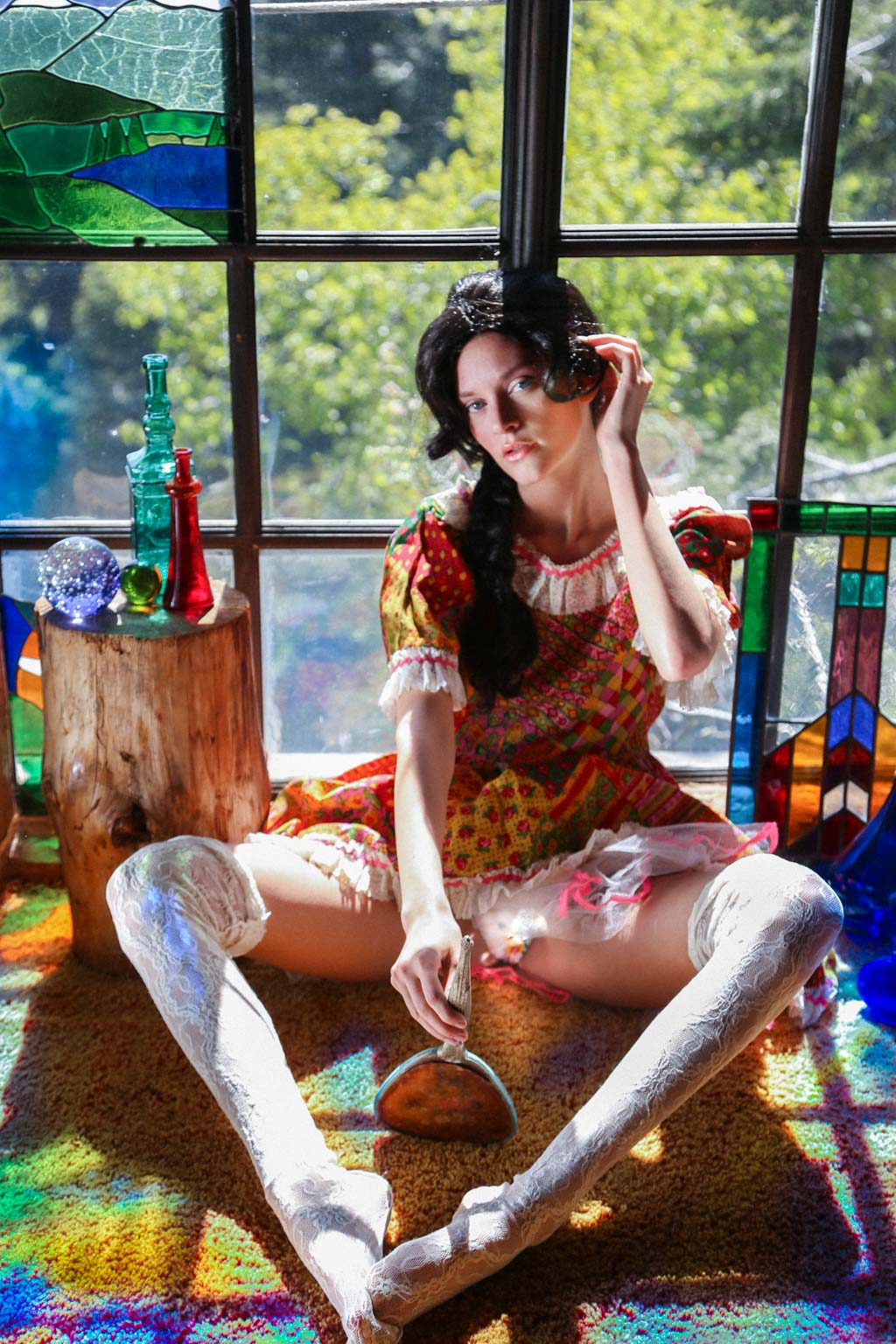 fashion editorial in bohemian rustic cabin shot by fashion photographer los angeles heather van gaale. the girl is surrounded by reflections of colorful light and stained glass while she looks at herself in the mirror.