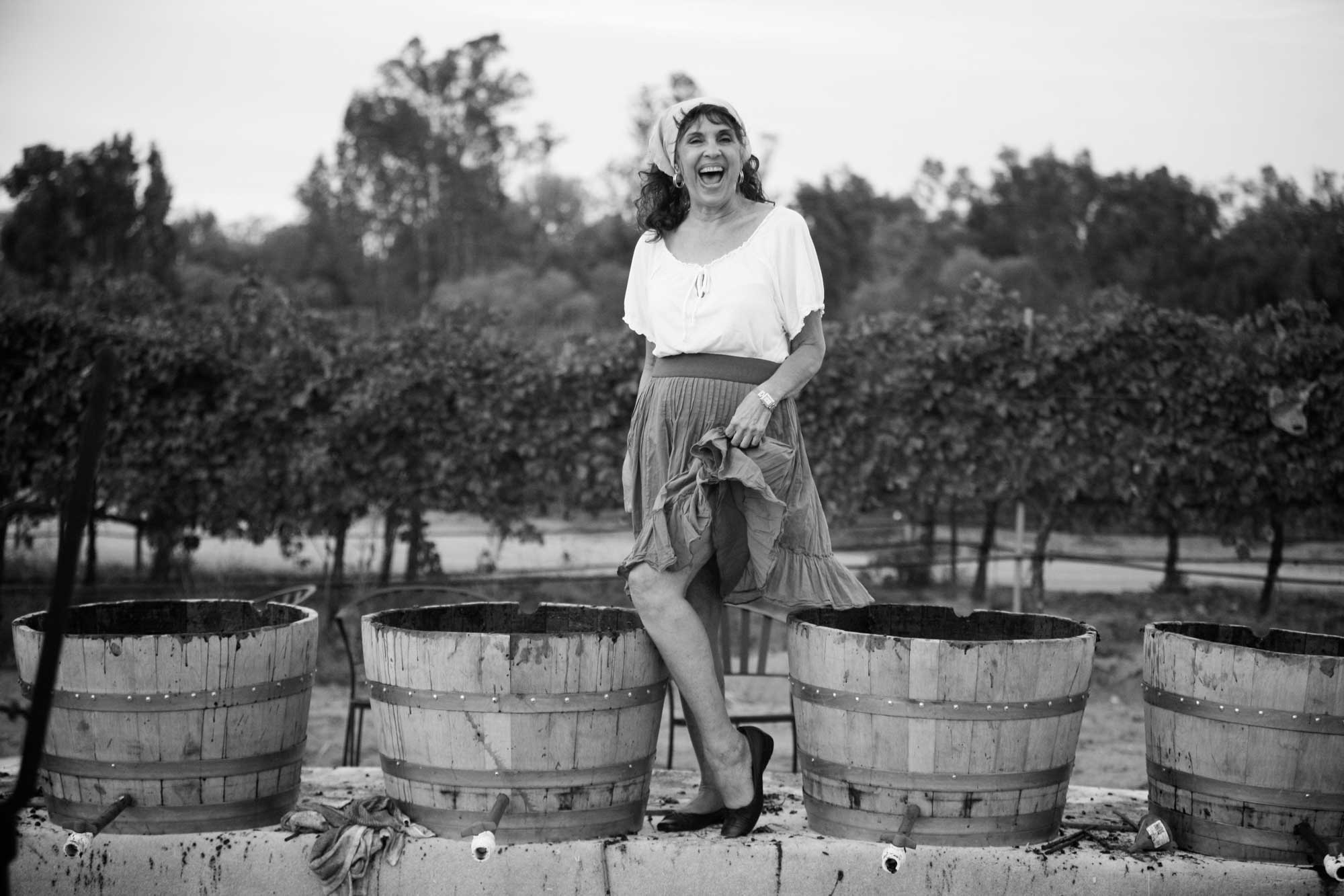 crush,grape stomp,vineyards,wine barrels,kegs,italian woman,60 year old